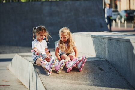 Having a rest. On the ramp for extreme sports. Two little girls with roller skates outdoors have fun.
