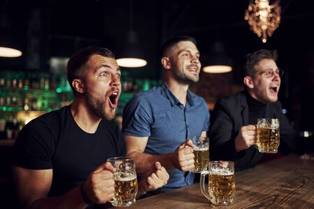 Celebrating victory. Three sports fans in a bar watching soccer. With beer in hands. Standard-Bild