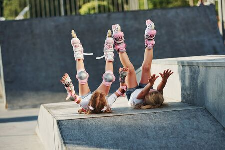 Legs up. Feeling free. On the ramp for extreme sports. Two little girls with roller skates outdoors have fun.