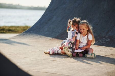 Relaxing and have conversation. On the ramp for extreme sports. Two little girls with roller skates outdoors have fun.
