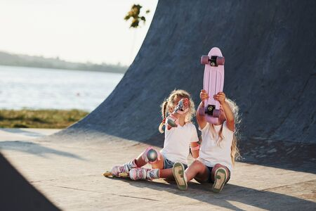 Trying new skate. Two cute female kids have fun outdoors in the park.