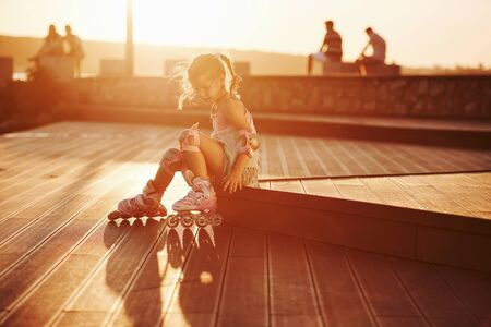 Happy cute kid with her roller skates. Unbelievable sunlight.