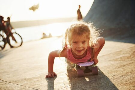 First attempts. Sunny day. Kid have fun with skate at the ramp. Cheerful little girl.