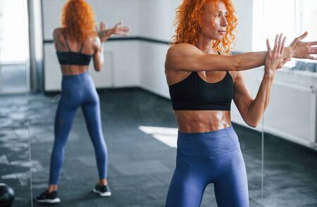 Ejercicios de calentamiento. Chica pelirroja deportiva tiene día de fitness en el gimnasio durante el día. Tipo de cuerpo musculoso.