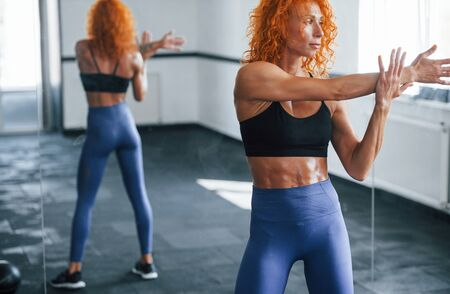 Warm up exercises. Sporty redhead girl have fitness day in gym at daytime. Muscular body type.