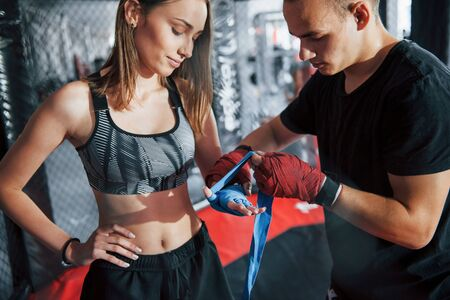 Wrapping bandages. Prepared for the fight. Athletic young people have exercise on the boxing ring. Stock Photo