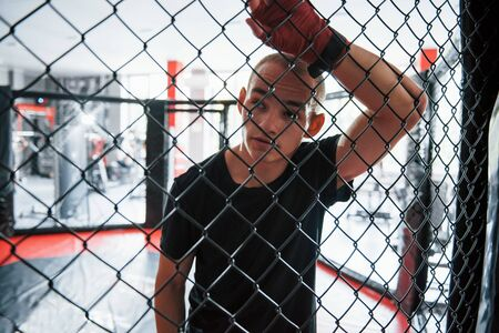 Taking a break. Sportsman at boxing ring have exercise. Leaning on the fence.