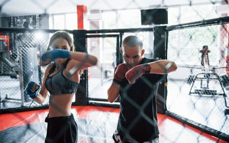 Athletic young people have daily exercise on the boxing ring.