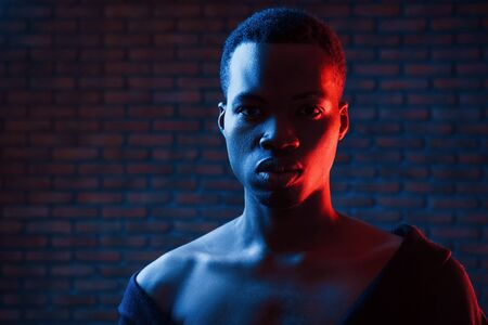 Confident guy. Futuristic neon lighting. Young african american man in the studio.