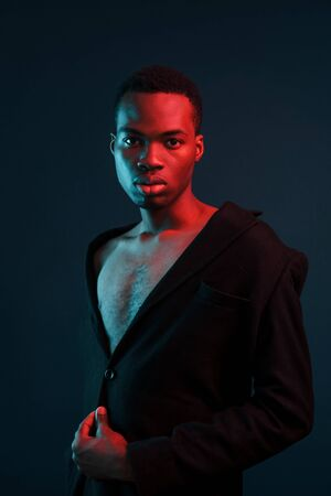 Confident and serious. Futuristic neon lighting. Young african american man in the studio. Stock Photo