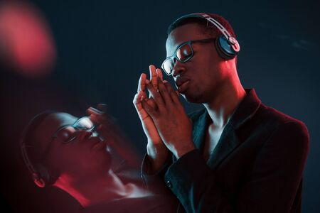 Enjoying listening music in headphones. In glasses. Futuristic neon lighting. Young african american man in the studio.