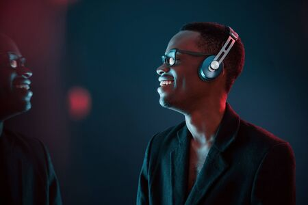 Enjoying listening music in headphones. In glasses. Futuristic neon lighting. Young african american man in the studio. Stock Photo