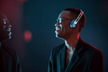 Genießen Sie das Hören von Musik über Kopfhörer. Bei Gläsern. Futuristische Neonbeleuchtung. Junger Afroamerikanermann im Studio.
