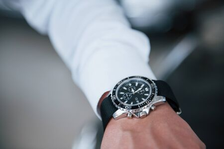 Close up photo of man's hand in suit with luxury watch.
