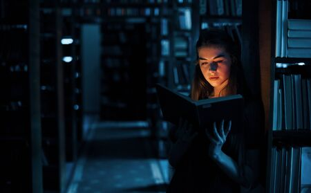Light from the book in dark room. Imagination conception. Female student is in library that full of books. Conception of education.