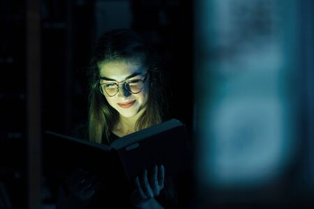 Mysterious green light comes from the book. Conception of creativity. Female student is in library. Conception of education. Imagens