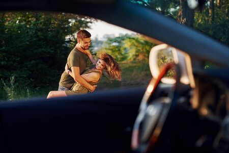 View through the cars window. Beautiful young couple have a good time in the forest at daytime.
