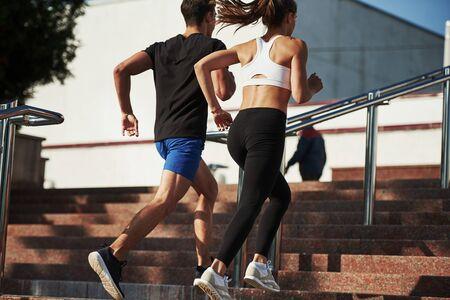 En las escaleras. El hombre y la mujer tienen un día de fitness y corren en la ciudad durante el día.
