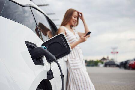Verwenden des Smartphones während des Wartens. Frau auf der Ladestation für Elektroautos tagsüber. Nagelneues Fahrzeug.