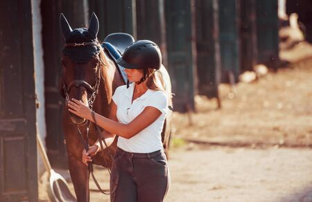 Horsewoman in uniform and black protective helmet with her horse.