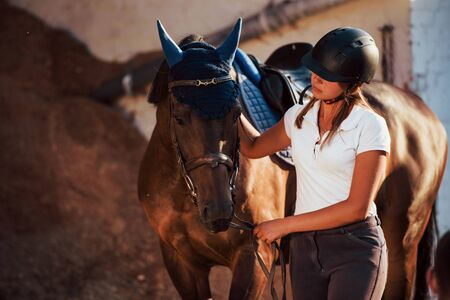 Ready for the ride. Horsewoman in uniform and black protective helmet with her horse. Stockfoto