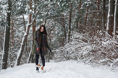 Friendship between human and animal. Woman in warm clothes walks the dog in the snowy forest. Front view.