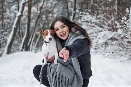 Please look into a camera, we are getting captured. Smiling brunette having fun while walking with her dog in the winter park.