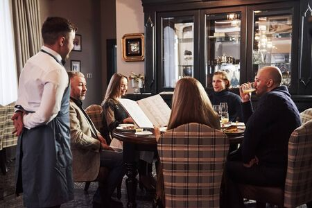 Kelner czeka na zamówienie. Przyjaciele rodziny miło spędzają czas w pięknej, luksusowej, nowoczesnej restauracji.