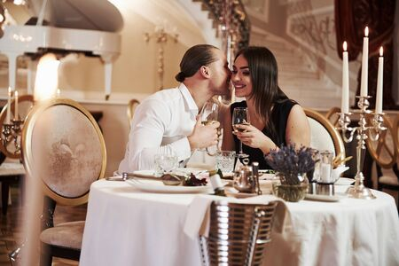 Lets keep it a secret. Beautiful couple have romantic dinner in luxury restaurant at evening time. Archivio Fotografico