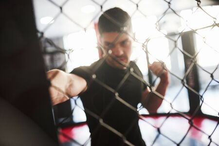 Blurred picture. Strong man is boxing in the gym behind the fence. Haves daily exercise. 版權商用圖片