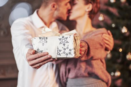 Kissing while holding gift box. Cute people. Nice couple celebrating new year in the new year decorated room.