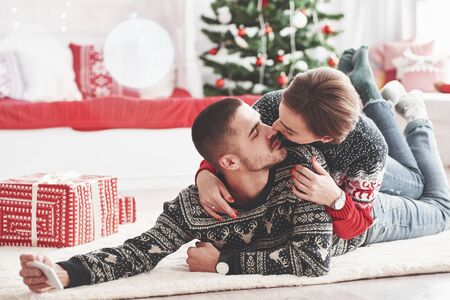 Making photo of cute kiss. Lovely young couple lying on the floor of living room at new year time with gift boxes.