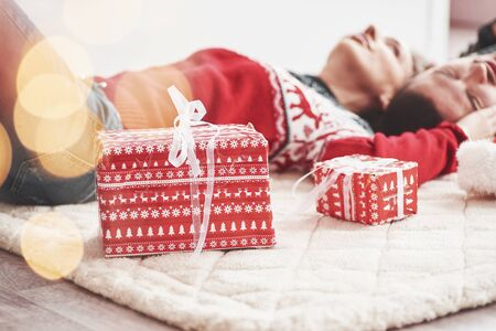 We can finally relax to feel peaceful and refresh. Lovely young couple lying on the floor of living room at new year time with gift boxes.