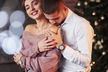 Woman smiles into the camera. Nice couple celebrating new year indoors with classic beautiful clothes on them. Imagens
