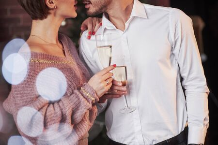 Holds glass with alcohol. Nice couple celebrating new year indoors with classic beautiful clothes on them. Imagens