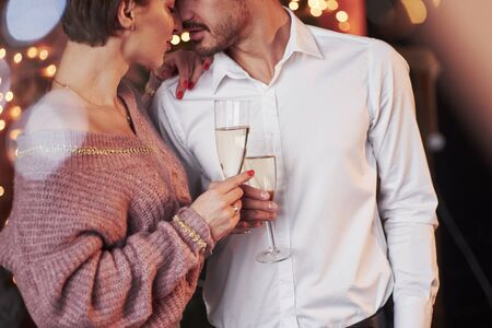 Champagne and love. Nice couple celebrating new year indoors with classic beautiful clothes on them.