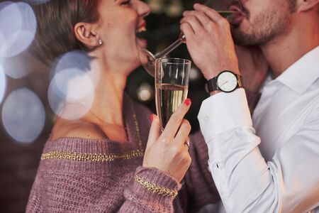 Drinking champagne. Nice couple celebrating new year in the new year decorated room. Imagens - 135889317