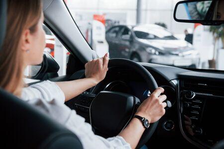 Ci sono molti veicoli proprio qui. Bella ragazza bionda seduta nella nuova auto con interni neri moderni.