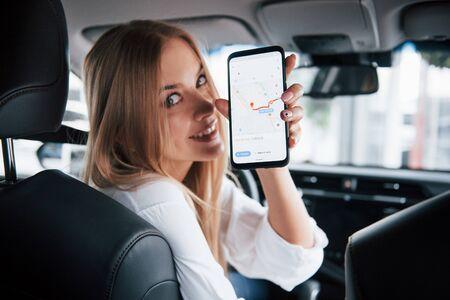 ¿Qué tan lejos puedo llegar? Hermosa chica rubia sentada en el auto nuevo con interior negro moderno.