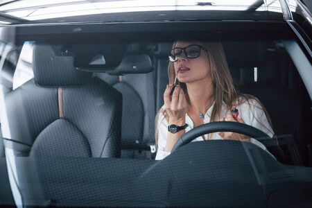 Prestigious businesswoman. Beautiful blonde girl sitting in the new car with modern black interior.