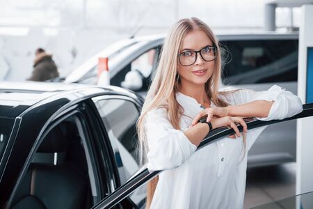 Cute girl in eyewear stands near the car in auto saloon. Probably her next purchase. Stock Photo
