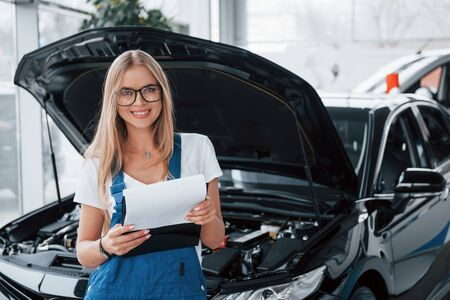 Machen Sie Ihre kaputten Fahrzeuge wieder großartig. Manager mit Notizblock, im weißen Hemd und blauer Uniform steht gegen Auto mit Kapuze.