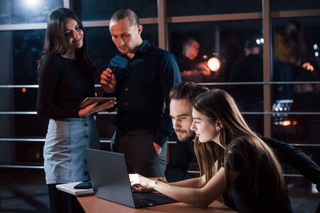 Important not to distract. Team of young business people works on their project at night time in the office. Foto de archivo - 136186628