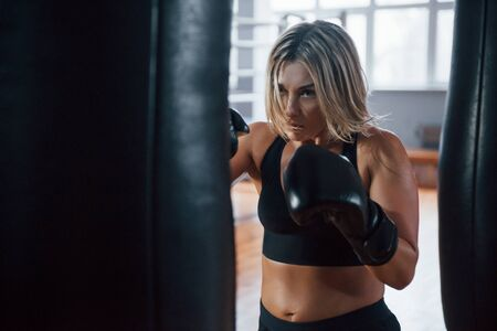 Sexy fighter. Female boxer is punching the bag. Blonde have exercise in the gym.