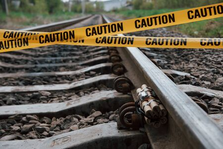 Do not touch. Dangerous explosive lying on the railway. Yellow caution tape in front.