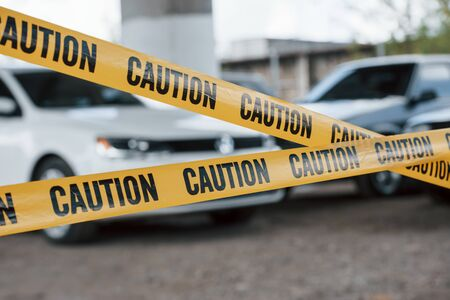 For the safety, do not enter this area. Yellow caution tape near the car parking lot at daytime. Crime scene. Stock Photo