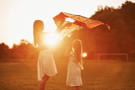 Orange colored sunset. Mother and daughter have fun with kite in the field. Beautiful nature.