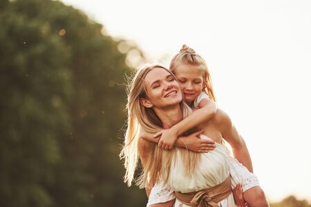 I hold you, dont worry. Mother and daughter enjoying weekend together by walking outdoors in the field. Beautiful nature.
