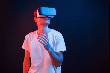 Looking up. Young man using virtual reality glasses in the dark room with neon lighting.
