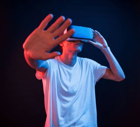Trying to reach some unreal objects. Young man using virtual reality glasses in the dark room with neon lighting.
